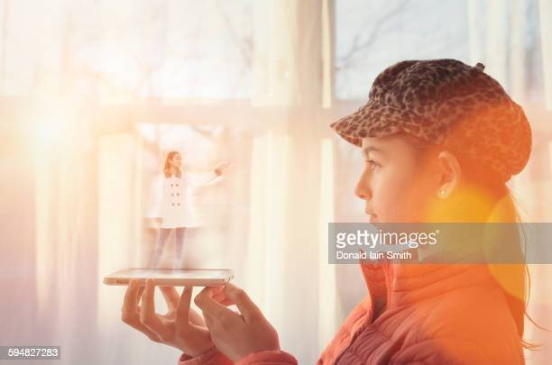 mixed race girl examining hologram projection - hologram stock pictures, royalty-free photos & images