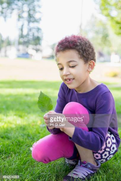 Mixed race girl examining leaf outdoors