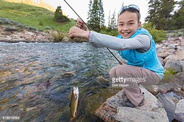 mixed race girl fishing in river - speckled trout stock photos and pictures