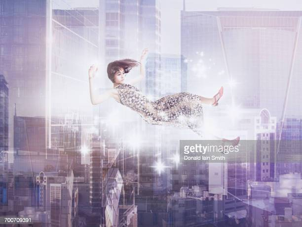 Mixed Race girl floating in city