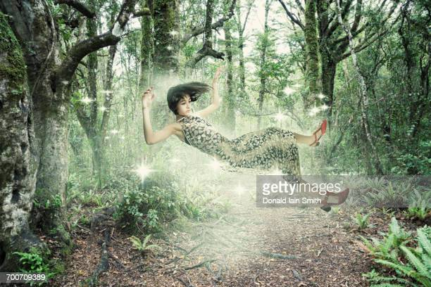Mixed Race girl floating in forest