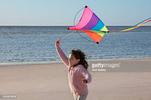 mixed race girl flying kite on beach - kite toy stock photos and pictures
