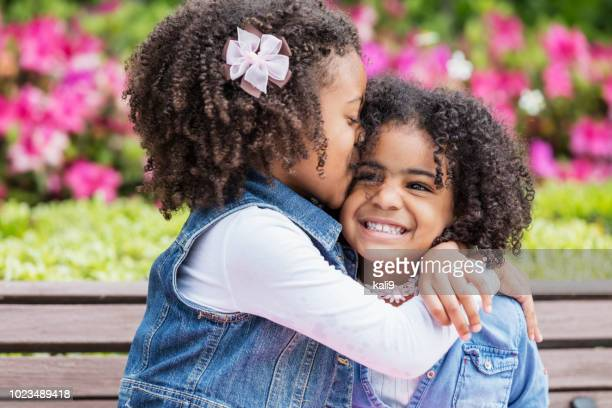 Mixed race girl giving little sister kiss on cheek