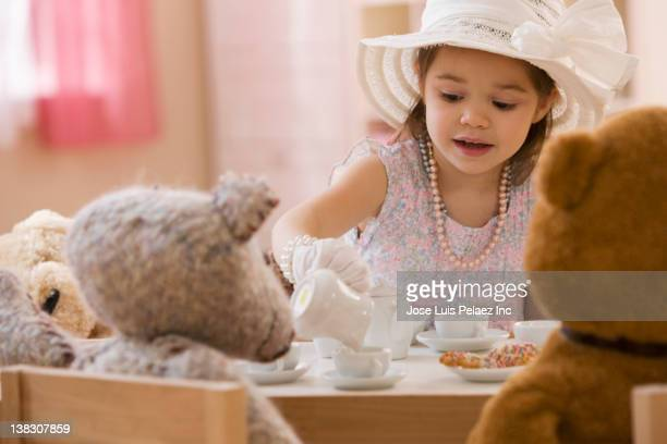 mixed race girl having tea party with stuffed animals - tea party stock pictures, royalty-free photos & images