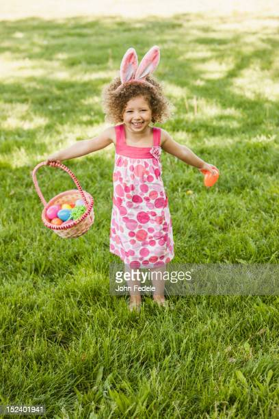 Mixed race girl holding basket of Easter eggs