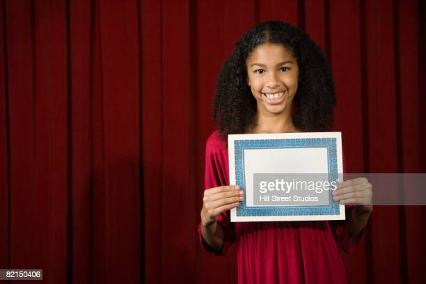 Mixed Race girl holding blank certificate on stage