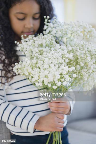Mixed race girl holding bouquet of flowers
