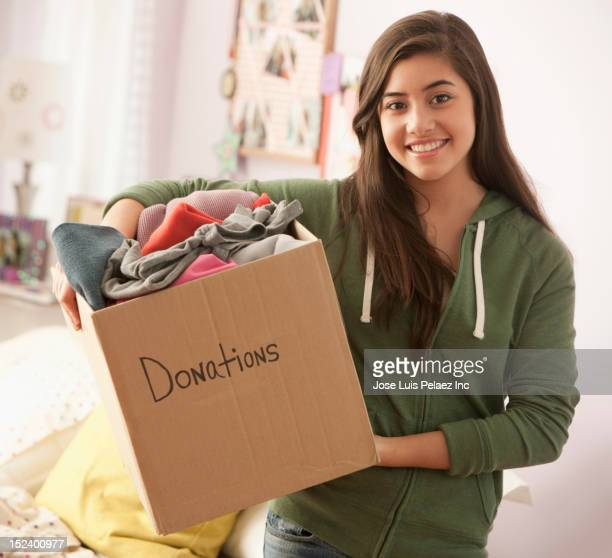 Mixed race girl holding box of donations for charity