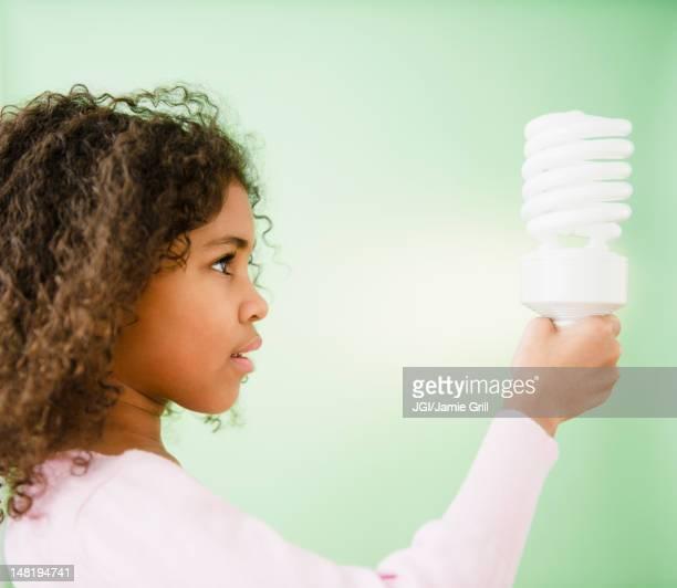 Mixed race girl holding CFL lightbulb