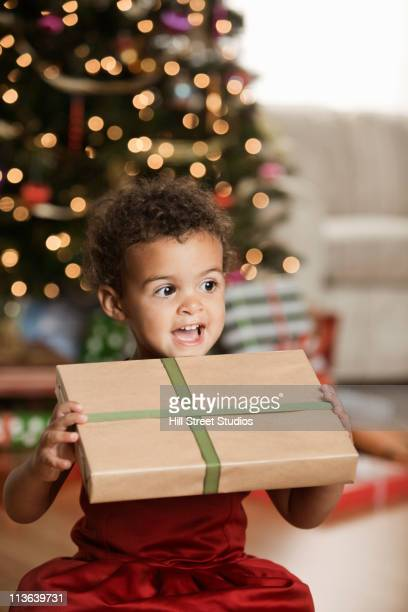 mixed race girl holding christmas gift - gardena california stock pictures, royalty-free photos & images