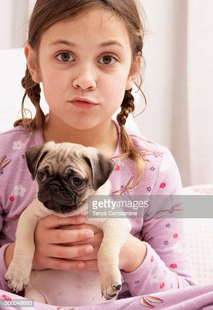 Mixed race girl holding dog on bed