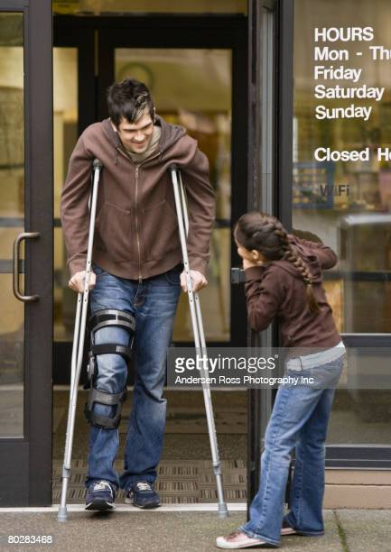 mixed race girl holding door for man on crutches - social grace stock pictures, royalty-free photos & images