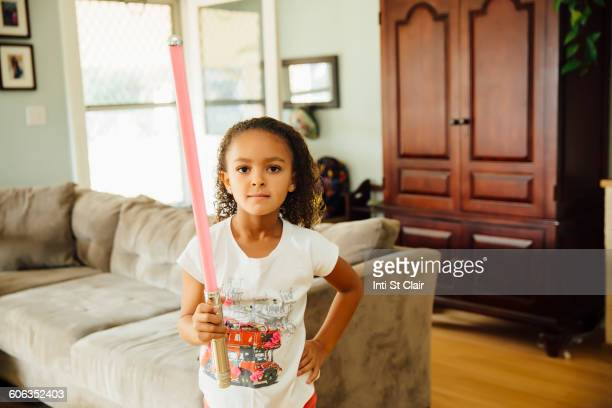 mixed race girl holding light-saber in living room - lightsaber stock pictures, royalty-free photos & images