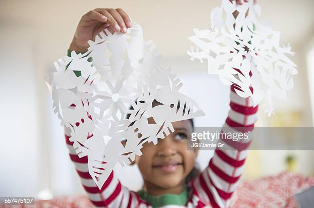 Mixed race girl holding paper snowflakes