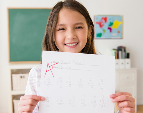 Mixed race girl holding paper with A+ grade - gettyimageskorea