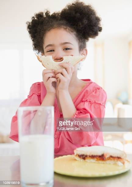 mixed race girl holding sandwich in front of face - peanut butter and jelly sandwich stock pictures, royalty-free photos & images
