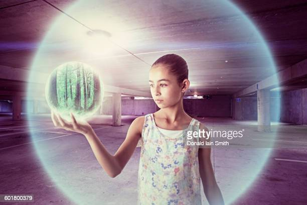 Mixed race girl holding sphere