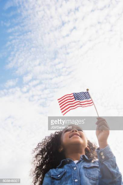 Mixed race girl holding United States flag outdoors