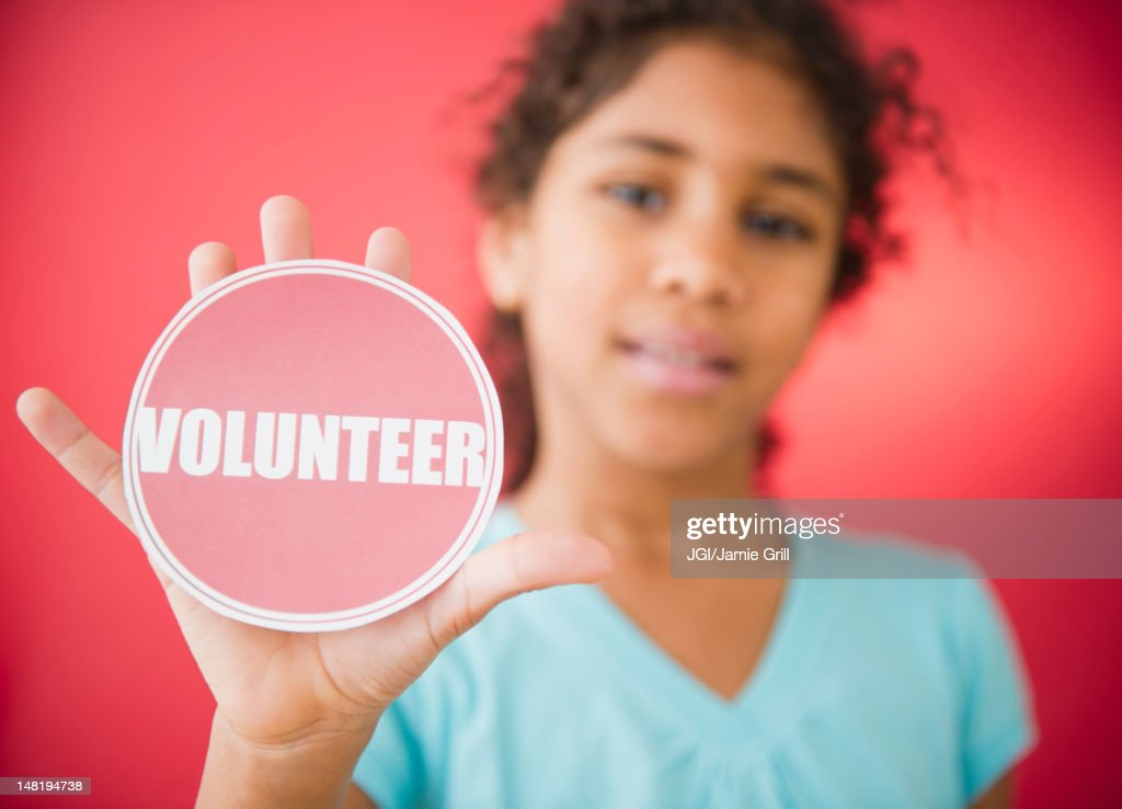 Mixed race girl holding volunteer sticker : Stock Photo