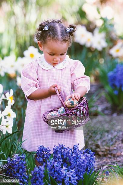 mixed race girl hunting for easter eggs - african american easter stock photos and pictures