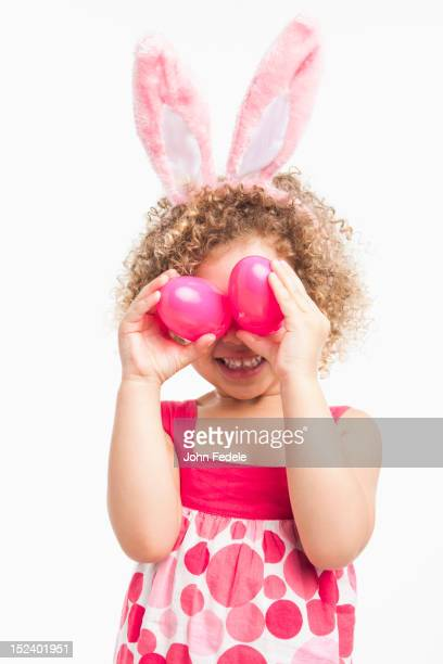 mixed race girl in bunny ears and holding easter eggs - african american easter stock photos and pictures