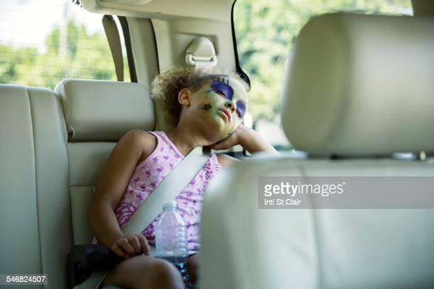 Mixed race girl in face paint sleeping in car back seat