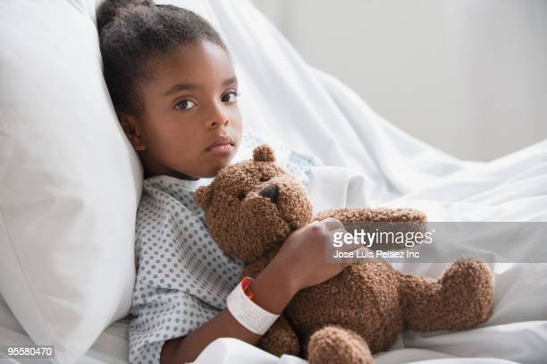 mixed race girl in hospital bed with teddy bear - girl in hospital bed sick stock photos and pictures