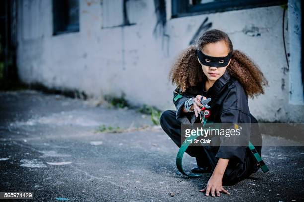 Mixed race girl in martial arts uniform and mask