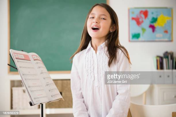 Mixed race girl in singing class