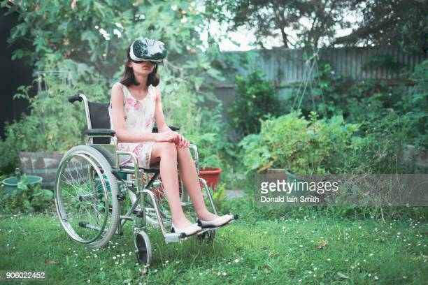 mixed race girl in wheelchair using virtual reality goggles in backyard - palmerston north new zealand stock pictures, royalty-free photos & images