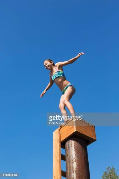 Mixed race girl jumping off platform