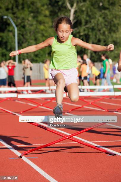 Mixed race girl jumping over hurdle