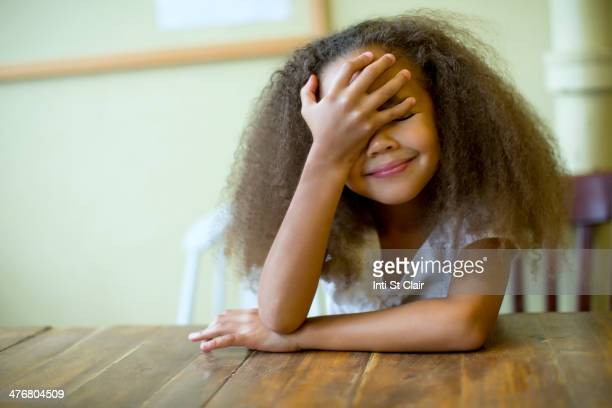 mixed race girl laughing at table - hands covering eyes stock pictures, royalty-free photos & images