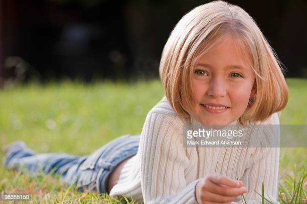 mixed race girl laying in grass - lying on front stock pictures, royalty-free photos & images