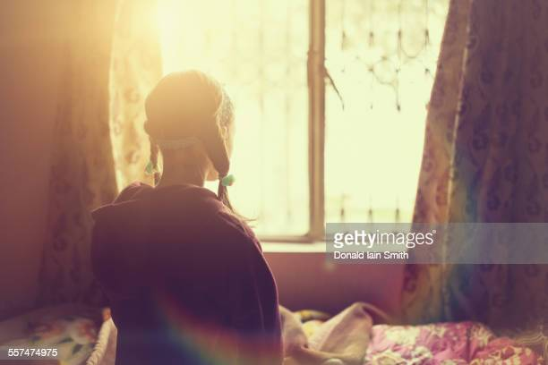 Mixed race girl looking out bedroom window