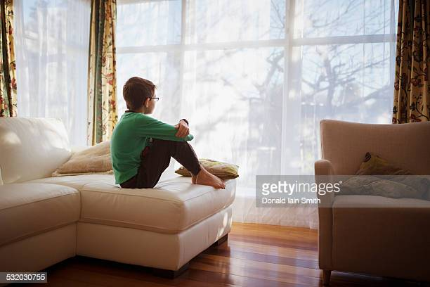 Mixed race girl looking out living room window