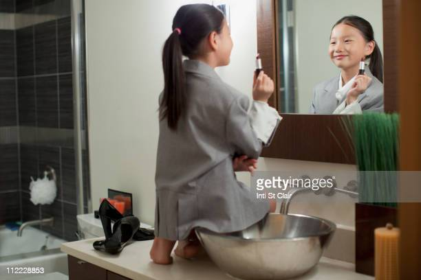 Mixed race girl on counter putting on lipstick