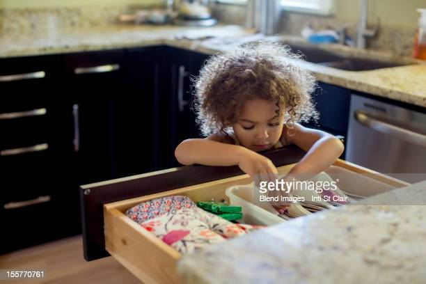 Mixed race girl opening kitchen drawer