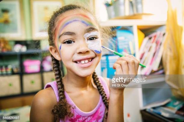 Mixed race girl painting her face in bedroom
