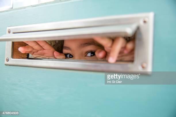 Mixed race girl peeking through mail slot