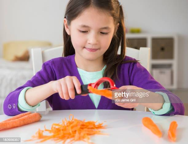 mixed race girl peeling carrots - dunschiller stockfoto's en -beelden