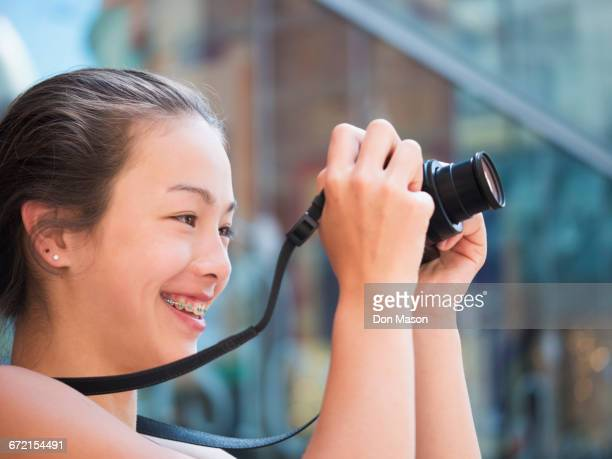 Mixed Race girl photographing outdoors with digital camera