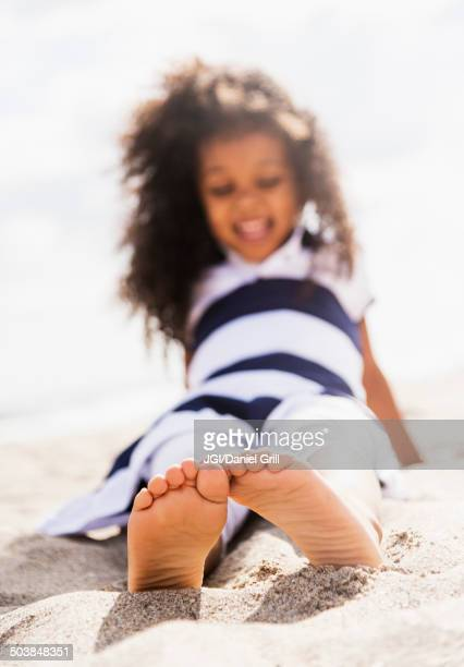 Mixed race girl playing in sand on beach