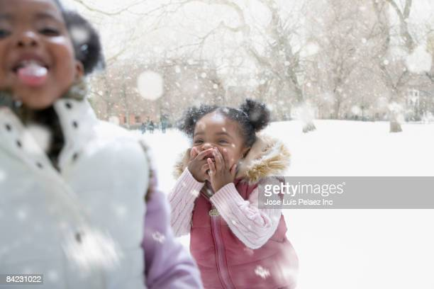 mixed race girl playing outdoors in falling snow - freezing motion photos stock pictures, royalty-free photos & images