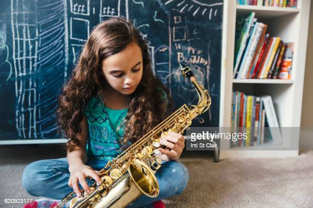 mixed race girl playing saxophone on floor - saxophone stock pictures, royalty-free photos & images