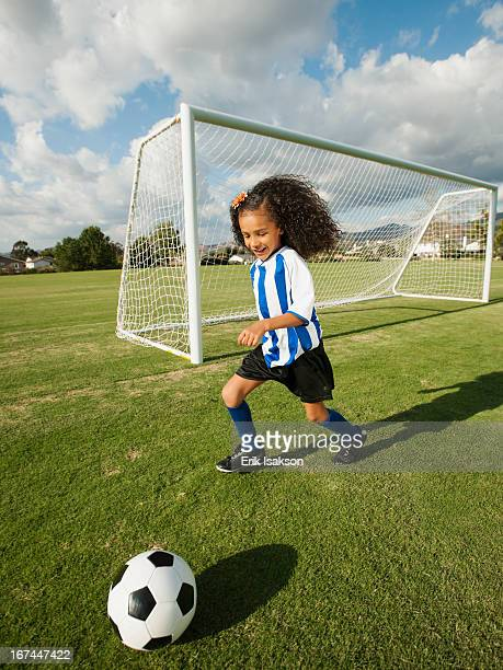 Mixed race girl playing soccer