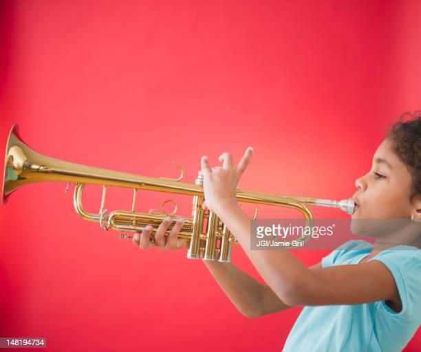 Mixed race girl playing trumpet