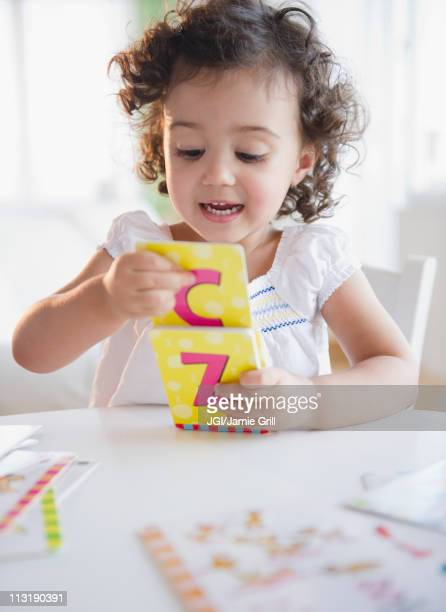 Mixed race girl playing with alphabet cards