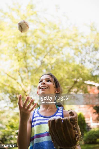 Mixed race girl playing with baseball and mitt outdoors