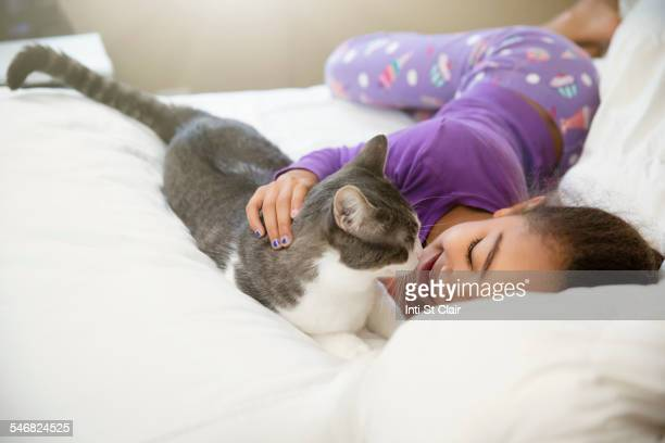 Mixed race girl playing with cat on bed